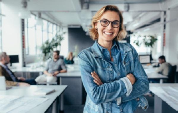 Счастливая женщина стоит в офисе