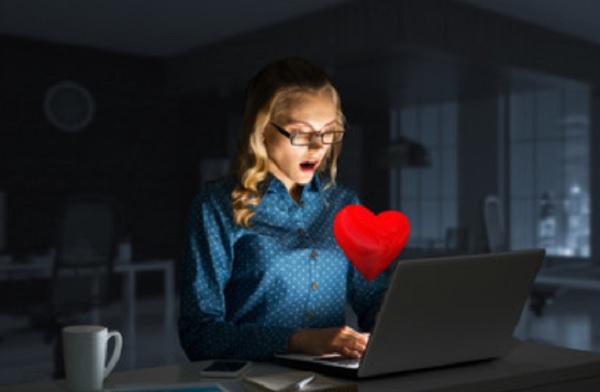 Женщина сидит перед ноутбуком. Ей прилетело сердечко