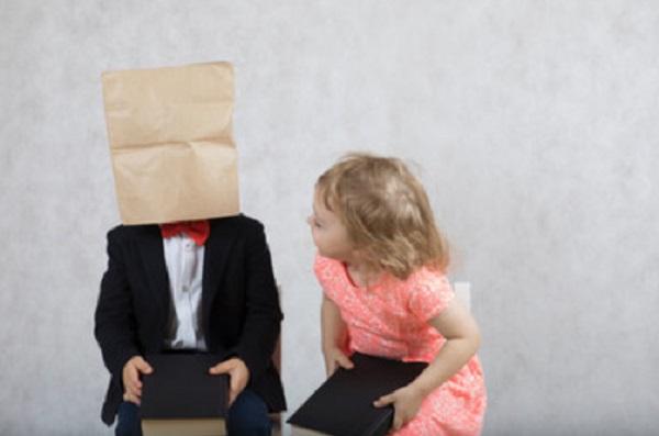 Девочка проявляет интерес к мальчику, который сидит с бумажным пакетом на голове