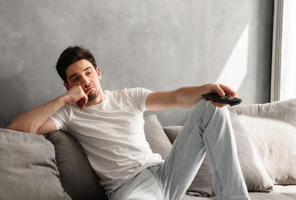 Ленивый мужчина сидит перед телевизором