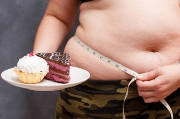 Мужчина с ожирением меряет объем своей талии, в одной руке держит тарелку с пирожными