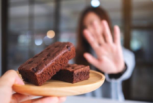 Женщина отказывается от тарелки с пирожным