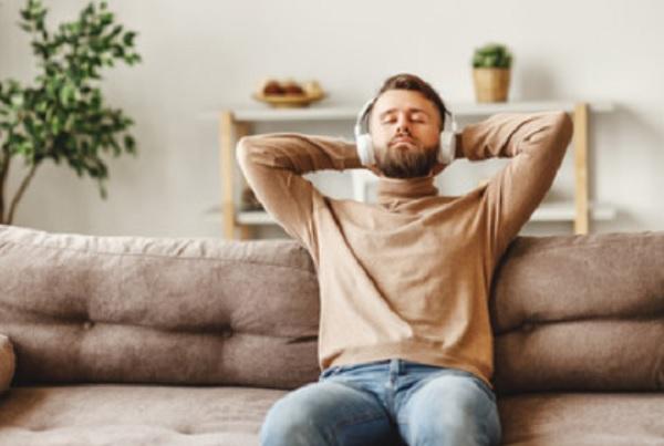 Мужчина сидит на диване и слушает музыку