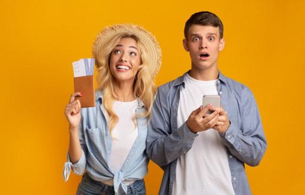 Парень в шоке с открытым ртом, девушка счастливая, держит билеты в руке