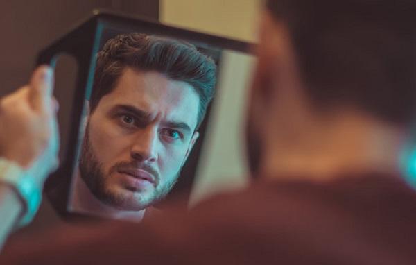 Мужчина смотрит на свое отражение
